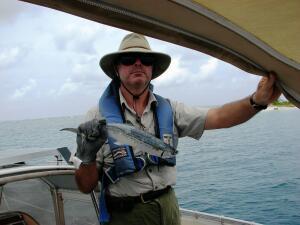 Triumphant fisherman with rainbow runner